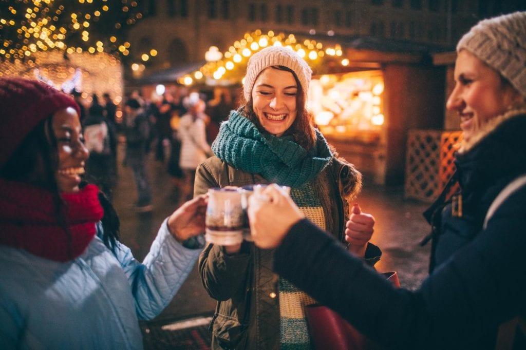 Gruppe mit Glühwein am Weihnachtsmarkt in Wien